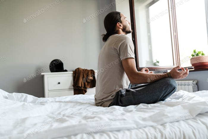 Young man meditating in bedroom
