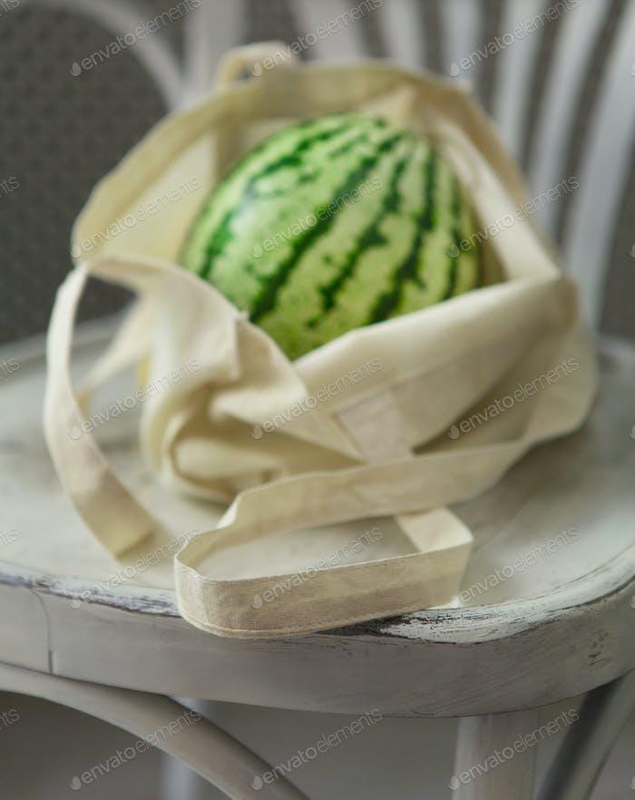 Bio große Wassermelone in Null Waste Einkaufstasche auf Stuhl
