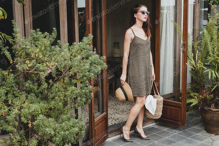young beautiful stylish woman in resort hotel, wearing trendy dress