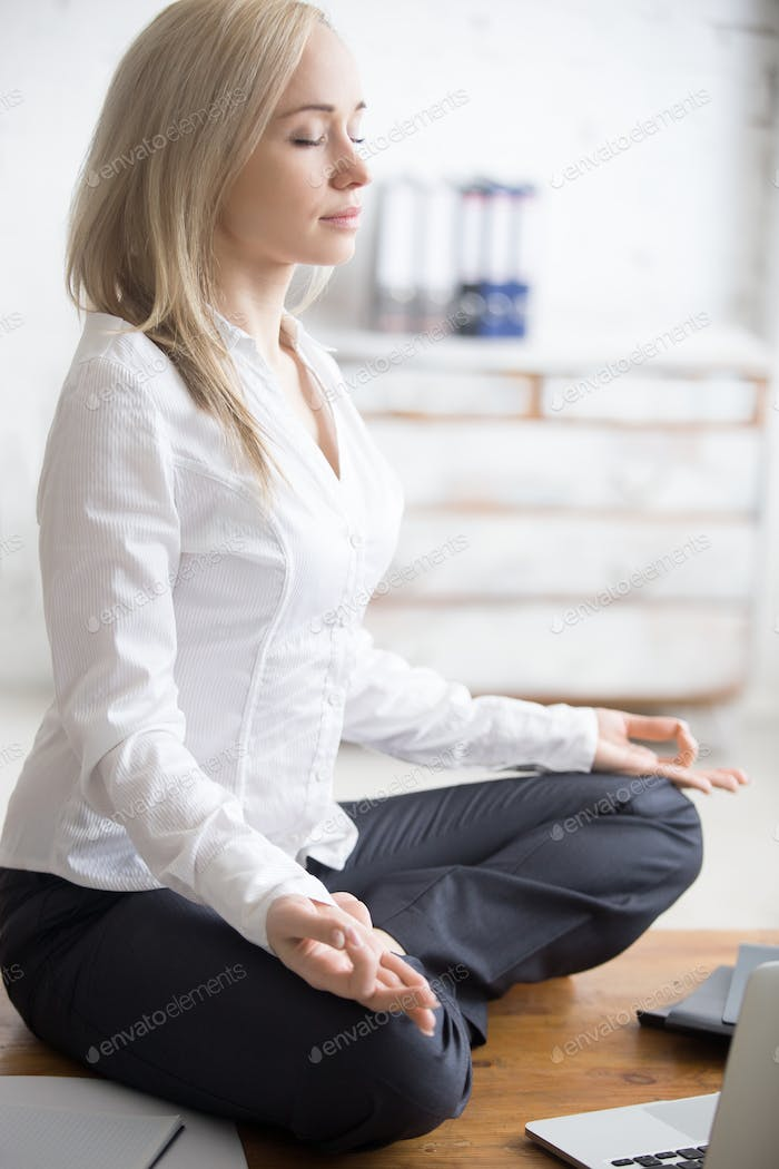 Business woman sitting in padmasana pose