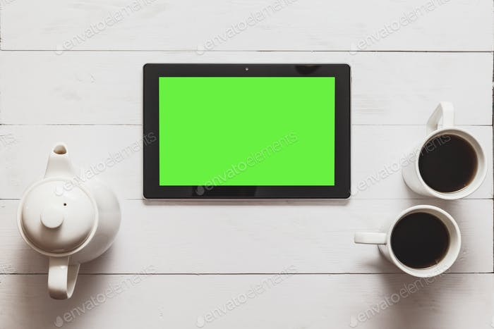 Black tablet with blank green screen and hot tea, teapot on loft wood table in cafe