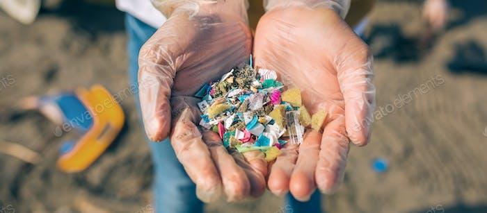 Manos con microplásticos en la playa
