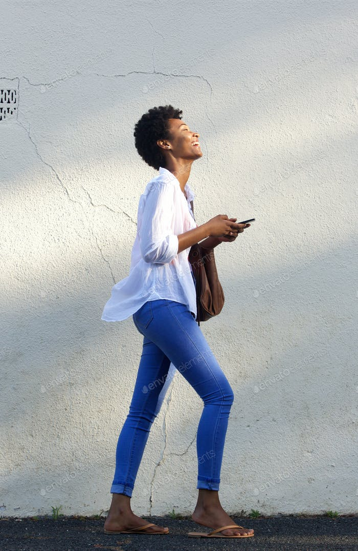 Smiling black woman walking on street with a mobile phone