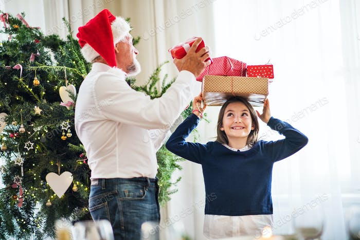 A senior man with a Santa hat and a small girl with presents at Christmas time.