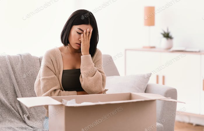 Sad young woman unpacking wrong parcel, delivery mistake