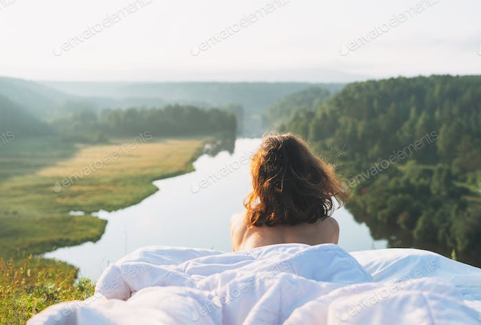 Young woman lying in bed with white bed linen in nature against beautiful landscape