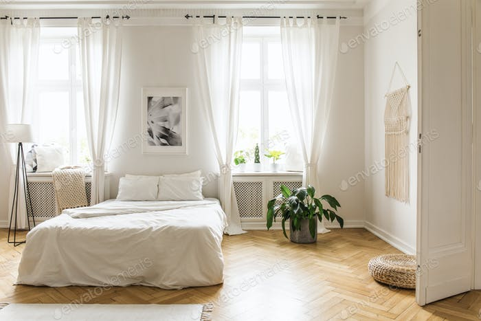 Poster between windows in bright bedroom interior with bed betwe