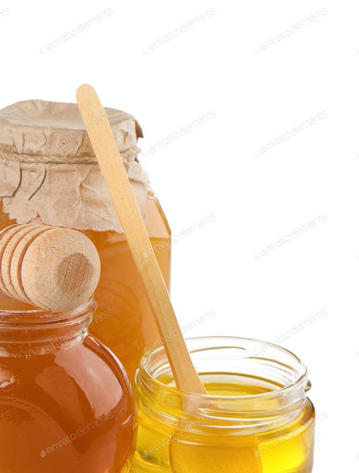glass pot full of honey isolated on white