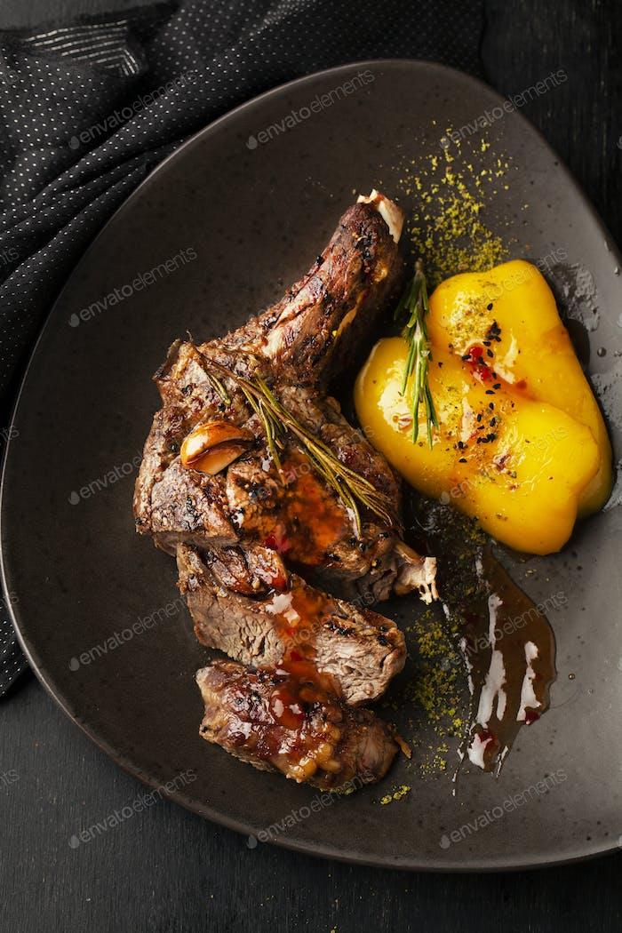 Roasted steak in frying pan on dark background