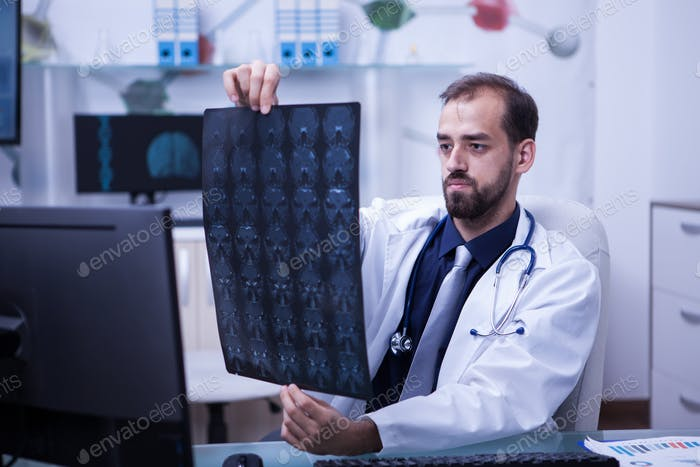 Portrait of handsome young doctor looking at a brain x ray
