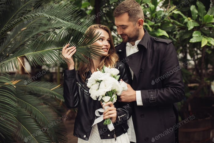 Young attractive man in trench coat and beautiful smiling woman