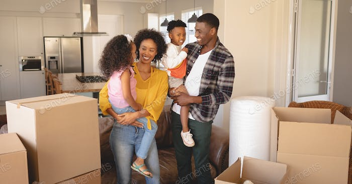 Front view of happy African American parents with their children and boxes moving in new house