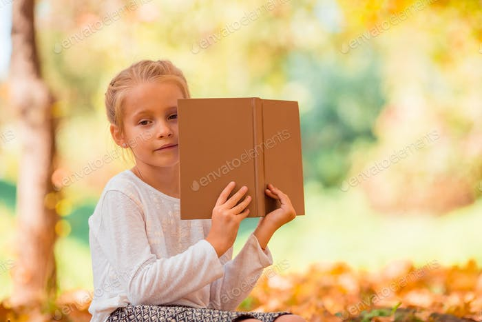 Portrait of adorable little girl outdoors at beautiful autumn