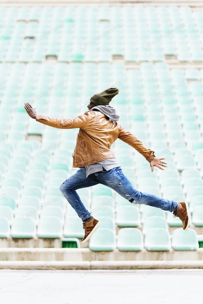 Amerikanischer Mann springt im Park.