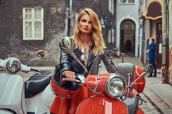 Sexy blondes Mädchen trägt stilvolle Kleidung stehen auf einer alten engen Straße mit zwei Retro-Scootern.