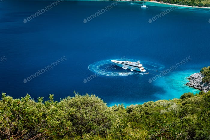 Luxury white yacht sail boat anchoring in a tranquil bay in deep blue water water, near picturesque