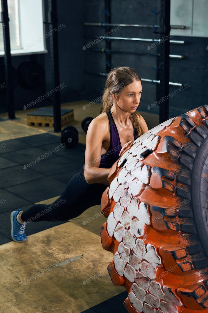 Strong Woman Flipping Tire in CrossFit