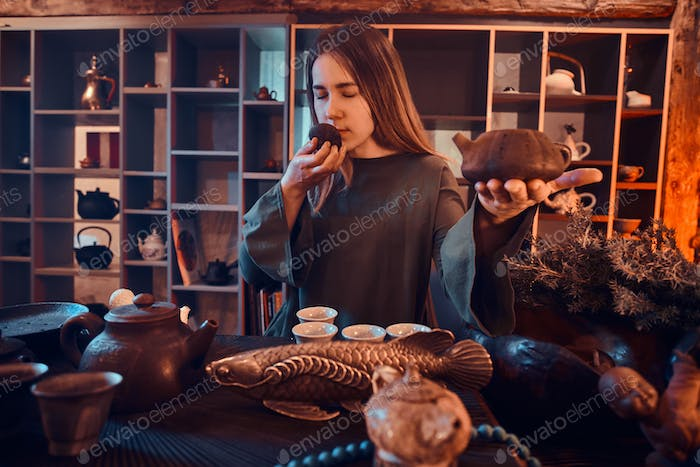 Oriental master wearing a dress in the dark room with a wooden interior. Chinese tea ceremony