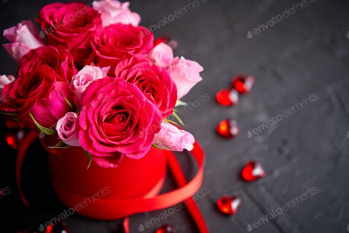 Pink roses bouquet packed in red box and placed on black stone background