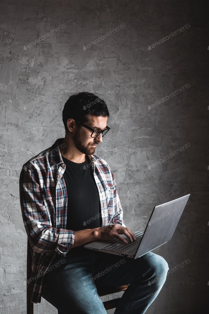 Casual man with laptop over gray background. internet, education, work, leisure