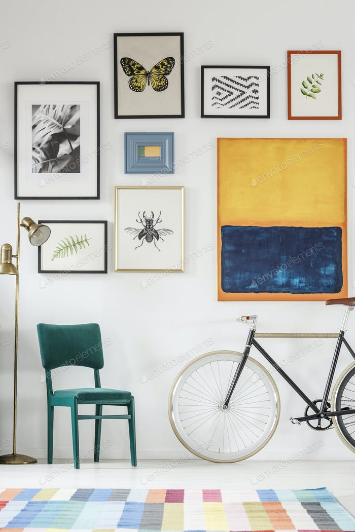 Green chair next to bike in living room interior with gallery of