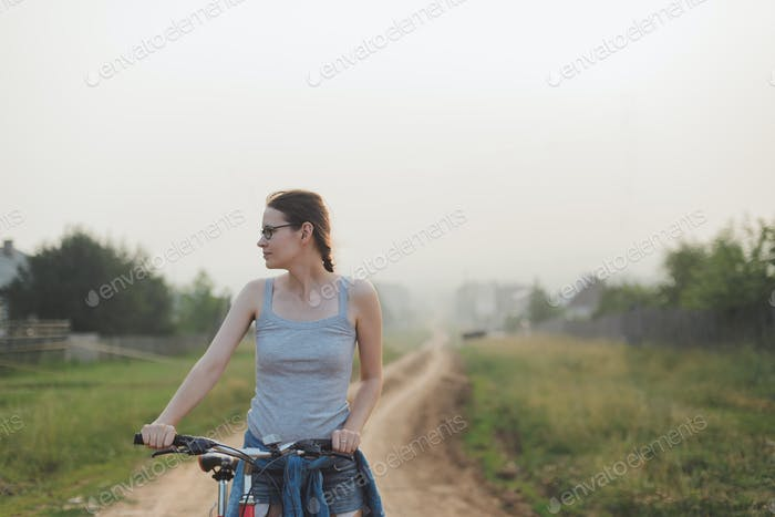 caucasian woman standing with bicycle in countryside road