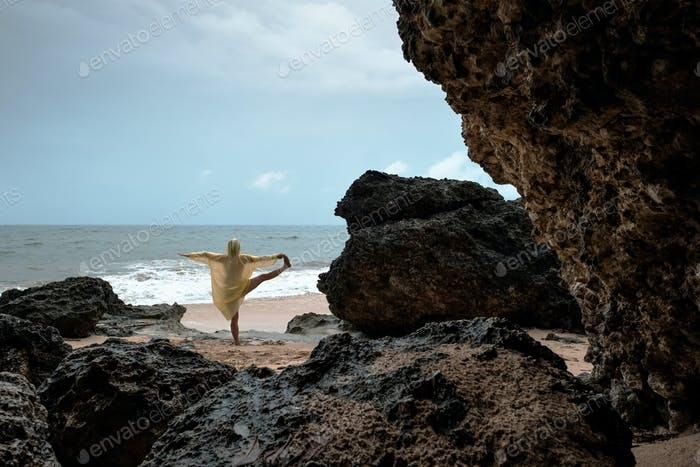 Woman in rain coat doing balance yoga asana on ocean beach during storm.