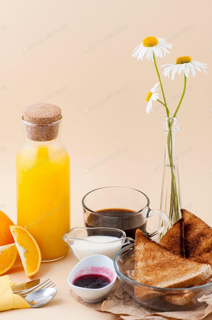 Set for breakfast: black coffee, milk, toast with jam, orange ju
