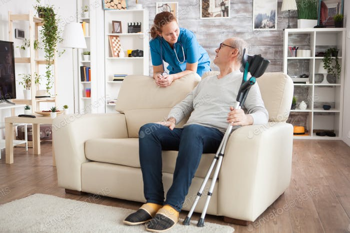 Old man sitting on couch holding his crutches