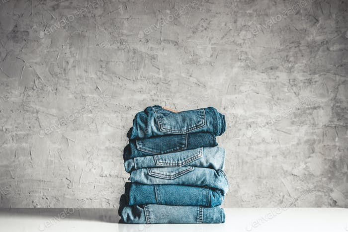 Stack of blue jeans on a gray background