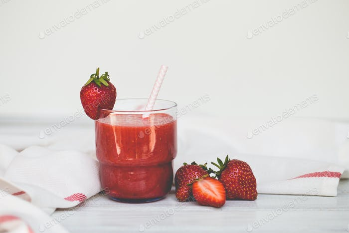 A glass of strawberry smoothie on a white wooden background
