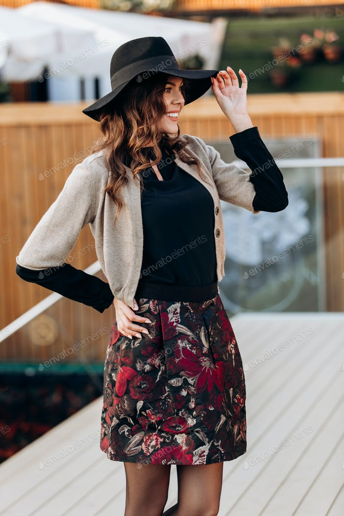 Stylish girl dressed in a black turtleneck, beige cape, stylish short skirt and black hat with wide