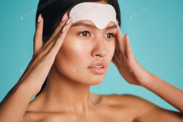 Close up attractive Asian girl confidently applying facial mask over colorful background