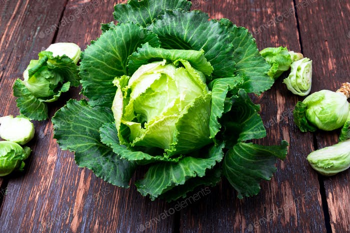 Fresh green cabbage big and small on wooden background. Top view. Copy space. Flat lay.