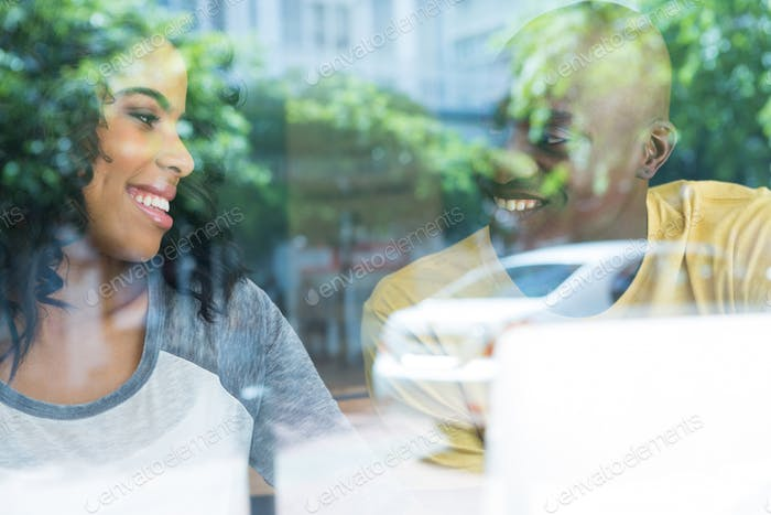 Couple looking at each other in coffee house seen through window