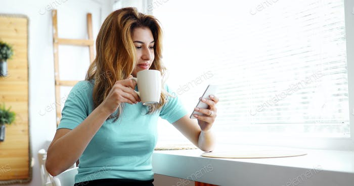 Beautiful blond woman drinking coffee and reading news