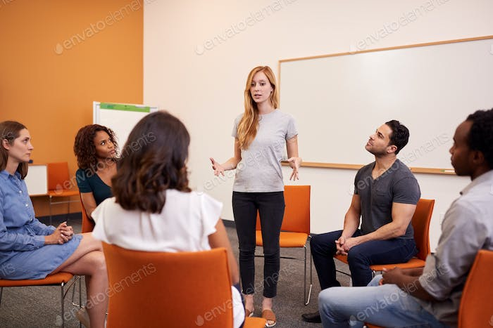 Woman Standing To Address Group Of Men And Women At Mental Health Group Therapy Meeting