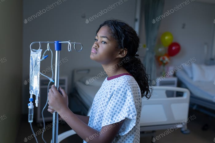 Bored sick mixed race girl standing in hospital ward with iv drip bag on stand looking out of window