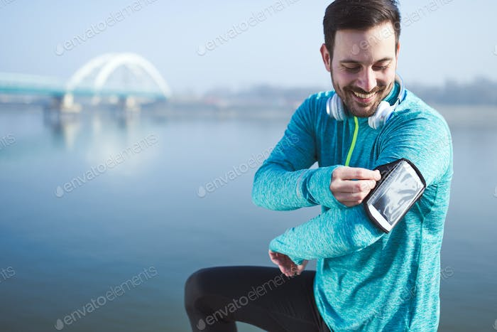 Sportsman using phone to listen to music while running and joggi