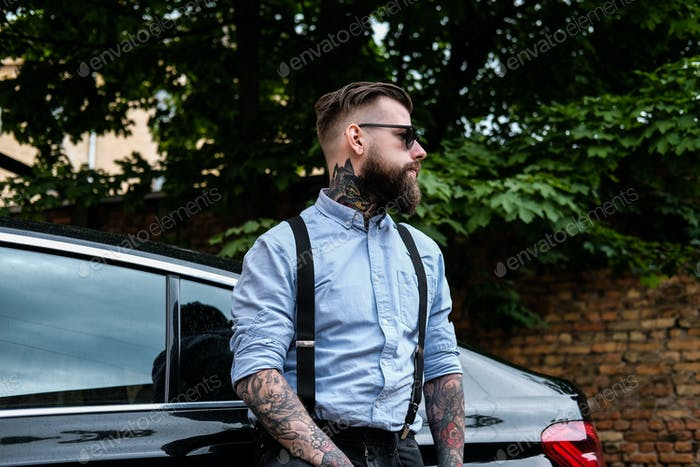 Attractive bearded man is leaning on his car.