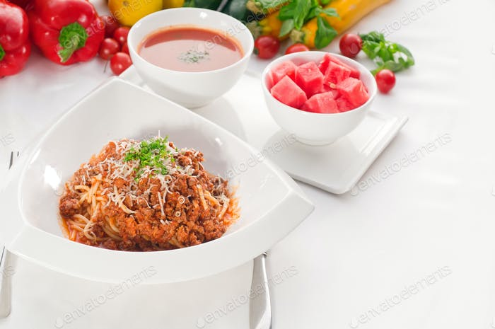 spaghetti with bolognese sauce with gazpacho soup and fresh vegetables on background