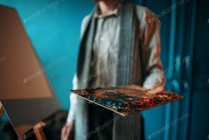 Male painter hand holds palette against the easel