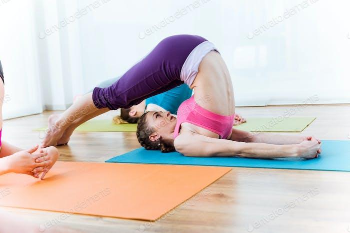 Group of people practicing yoga at home. Halasana pose.
