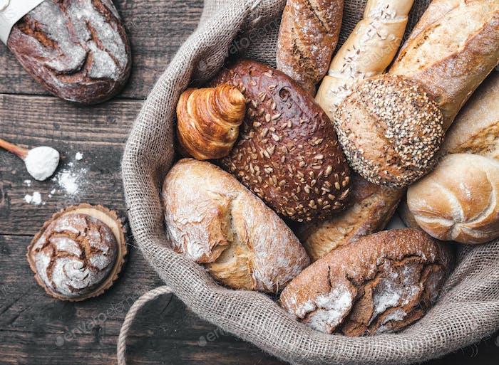 Delicioso pan fresco dentro de un saco sobre Fondo de De madera
