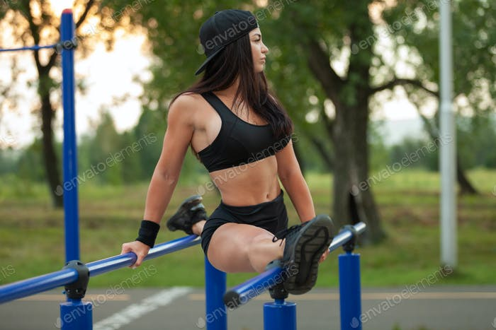 Athletic brunette woman shows stretching at public playground