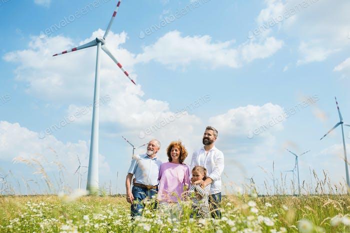 Multigeneration family standing on field on wind farm