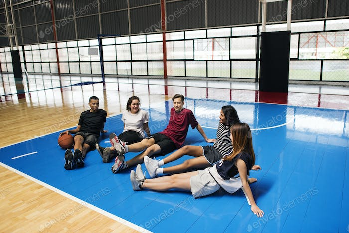Group of young teenager friends on a basketball court relaxing