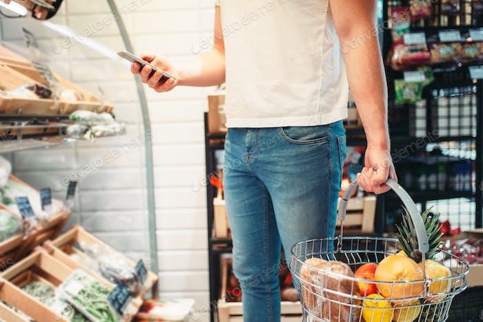 Comprador masculino con cesta y teléfono Móvil en las manos