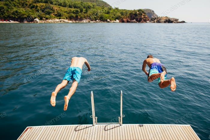 men jumping into sea water from yacht