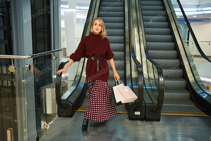 Attraktive stilvolle blonde Mädchen mit Einkaufstaschen auf Rolltreppe in modernen Einkaufszentrum